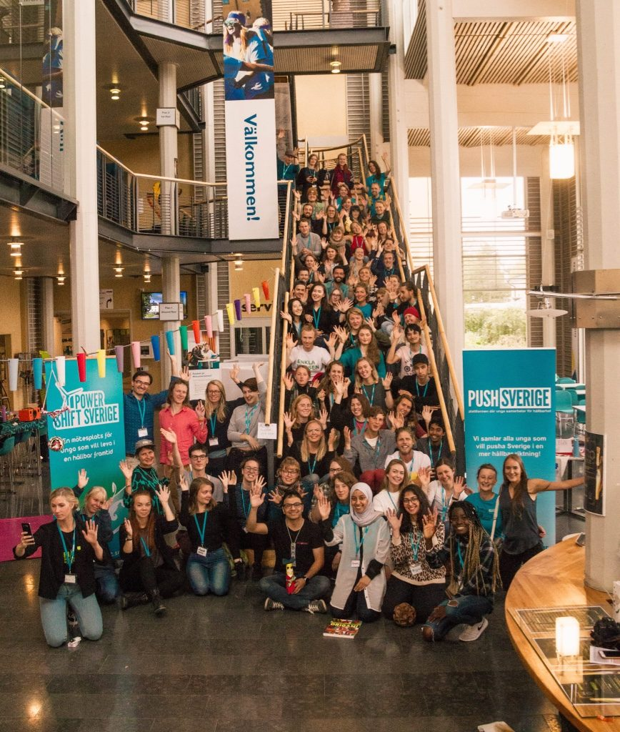 Fotografi från PowerShift 2017 i Östersund där alla deltagare sitter samlade på en trappa vid Mittuniversitetets lokaler.